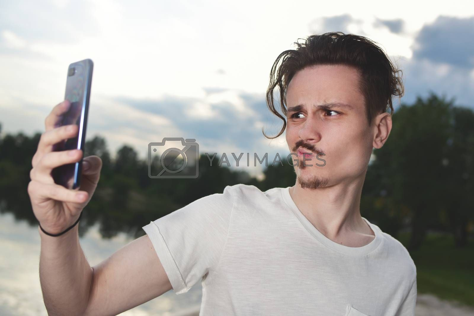 the guy grimaces into the camera.frustrated young handsome guy makes unsuccessful selfie on his smartphone in nature,