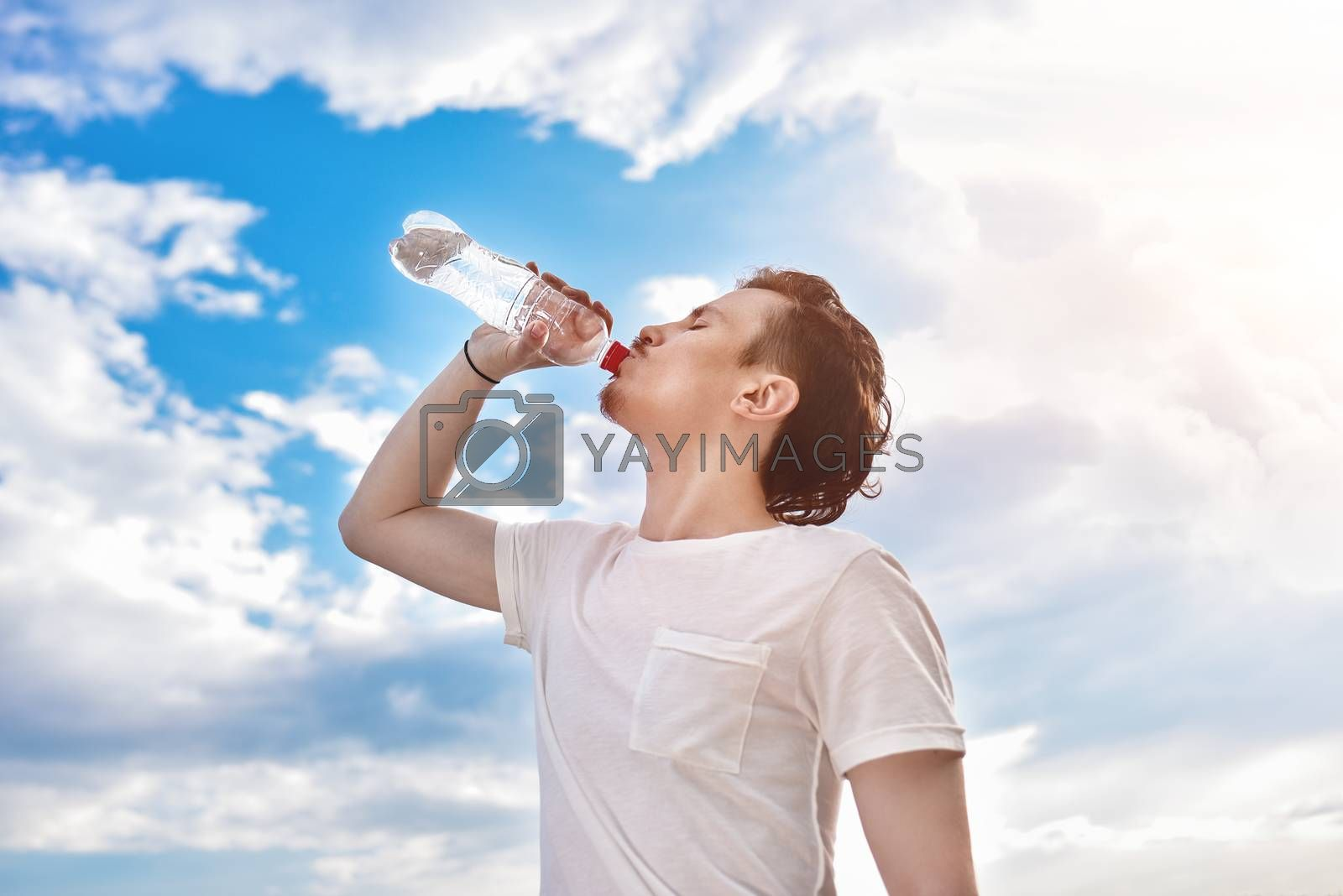young guy drinks fresh water against of the lake and the forest background. summer thirst. beautiful view