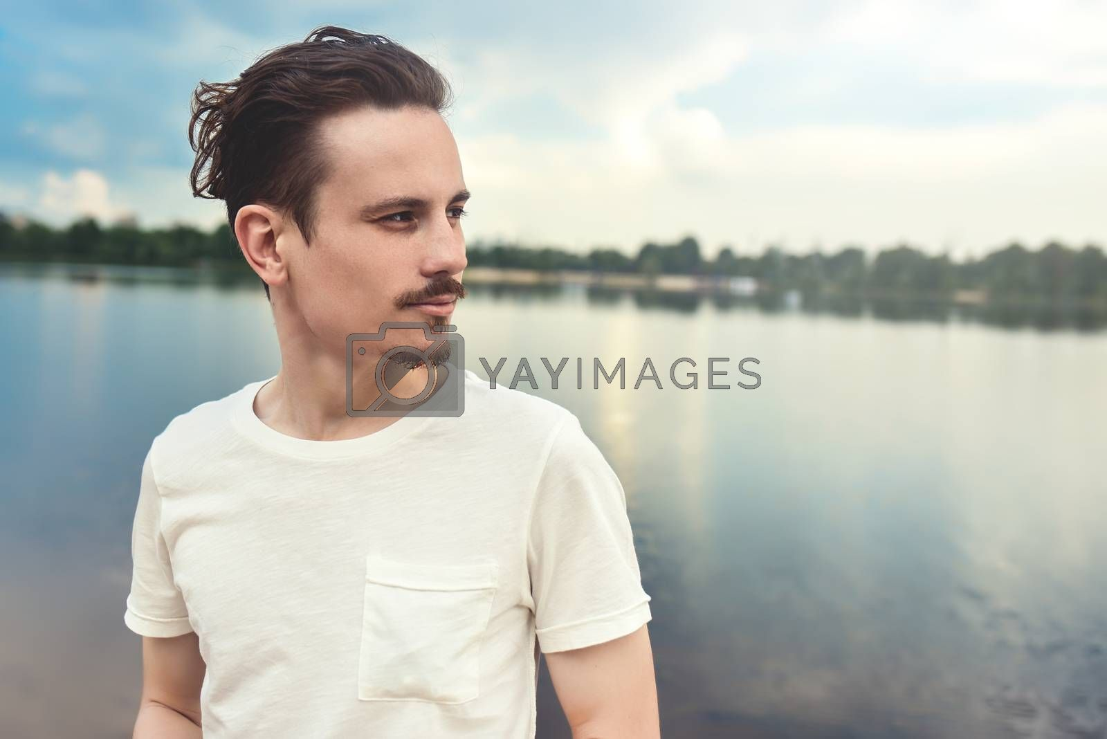 Portrait of Young Man Enjoys a beautiful view and looks into the distance near a lake and forest . summer . spring. nature