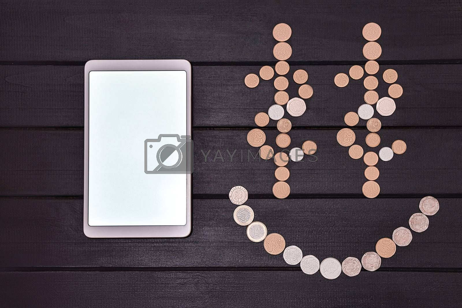 Financial success concept. Smartphone and Coins Formed A Smiley Face emoji on the table. Lucky day. success business. free copyspace