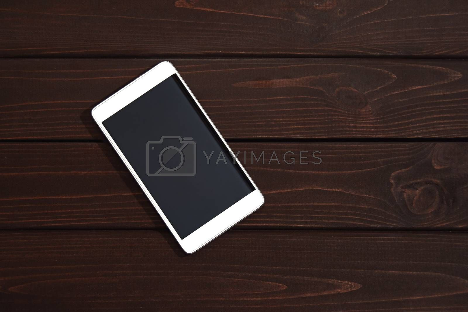 Mobile phone on wooden table background. Smartphone on wood old plank vintage texture background. top view