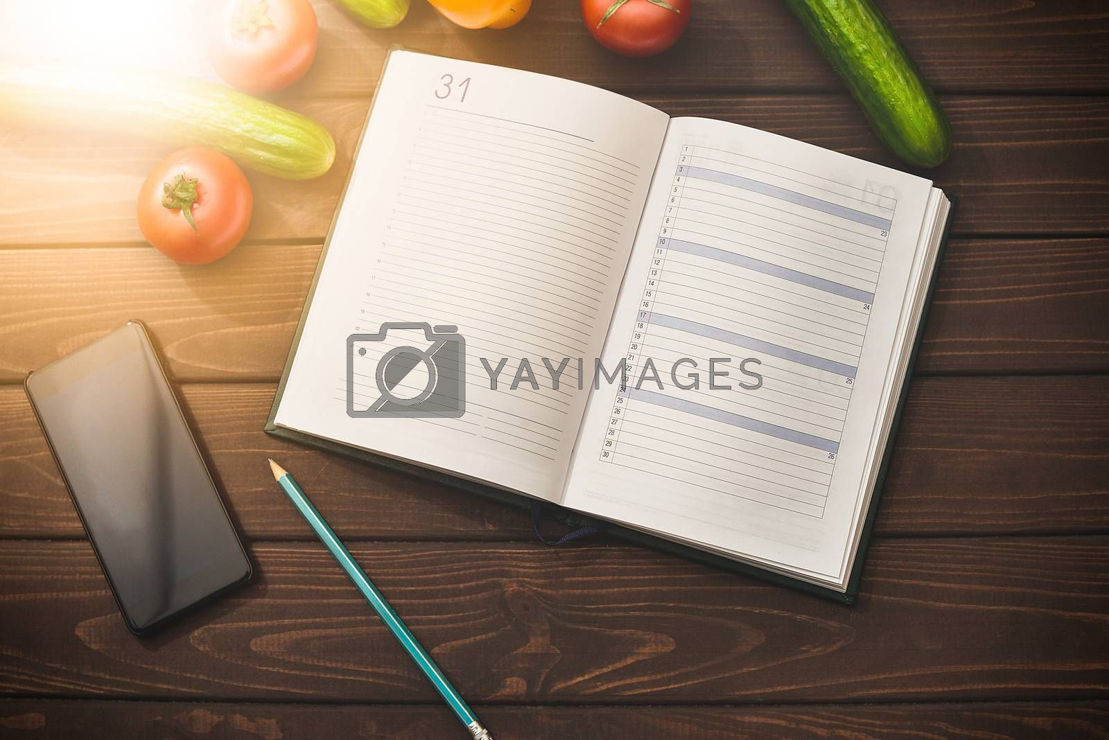 Dieting concept with a smartphone and a notepad and pen surrounded by lots of healthy fruit and vegetables.