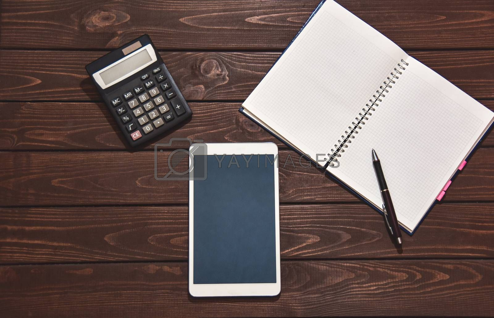 Top view of tablet, smartphone, calculator, notepad on wooden background, planning personal income, financial concept. typing on the calculator for money plan.
