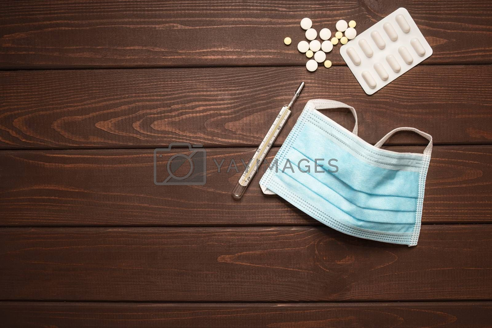 medical protective mask with medicines, thermometer on a wooden background,copy space by Nickstock