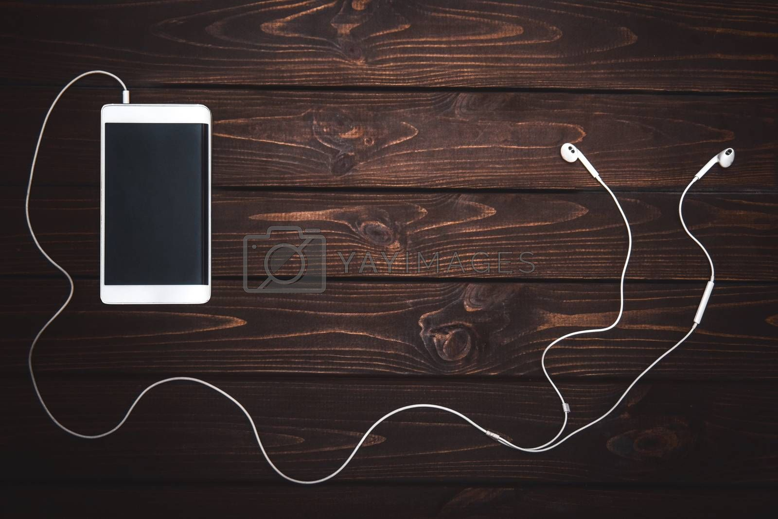 white smartphone with white headphones on wooden background- Image.Listening to music