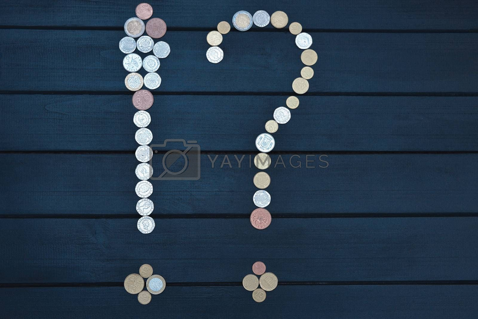 Scattered coins of different countries in the form of a question mark and an exclamation point on wooden table.