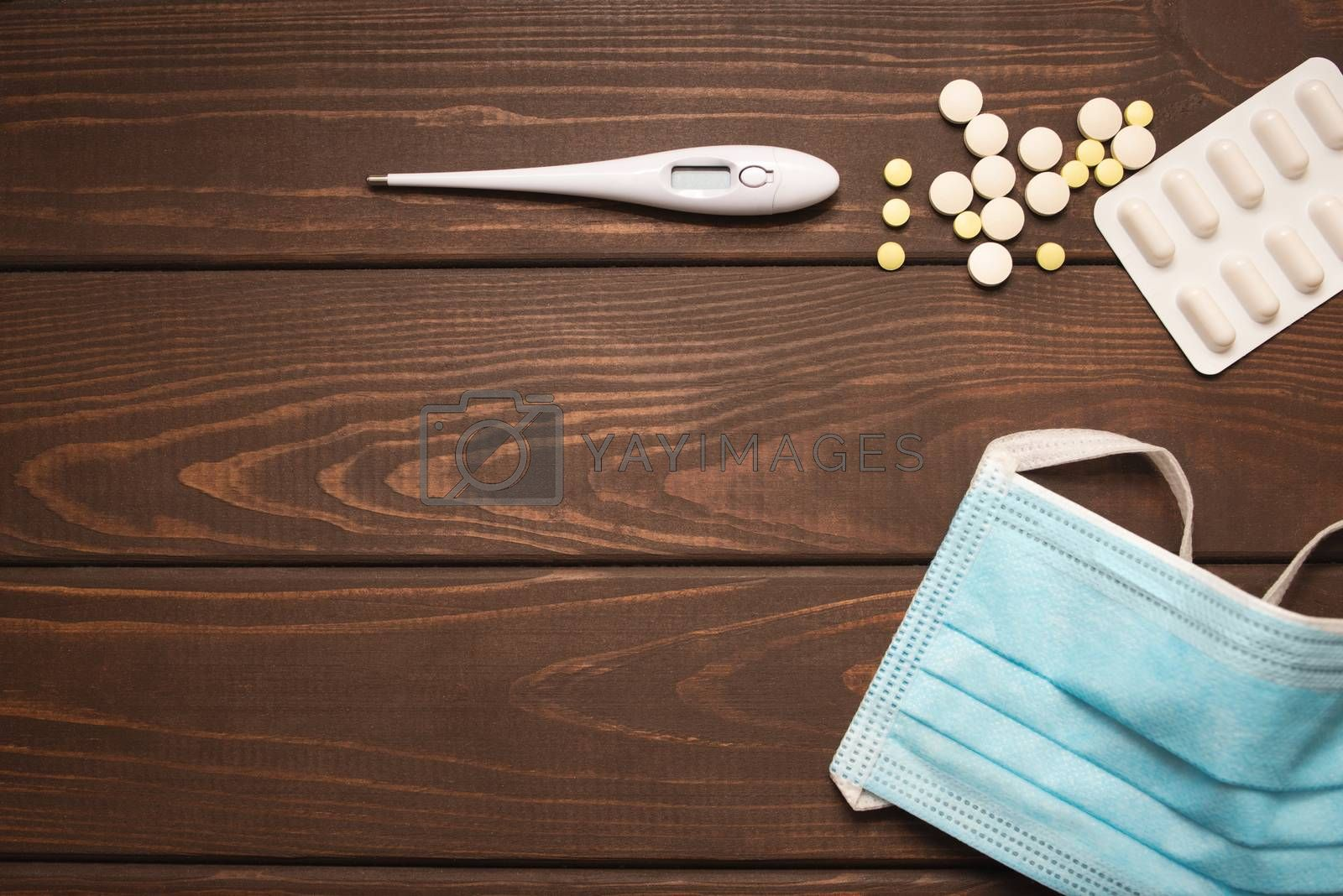 medical protective mask with medicines, thermometer on a wooden background, copy space