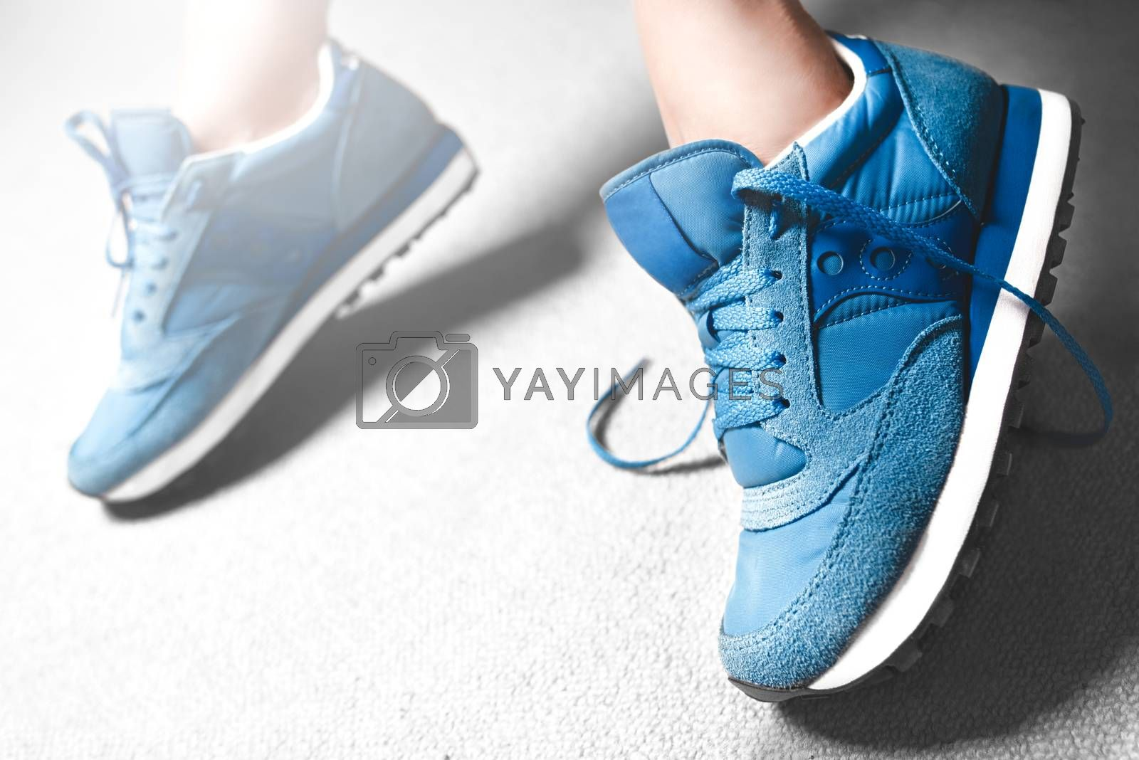 Close up women's legs on white background, blue Sneakers ,Women's shoes,spot focus. sport sneakers