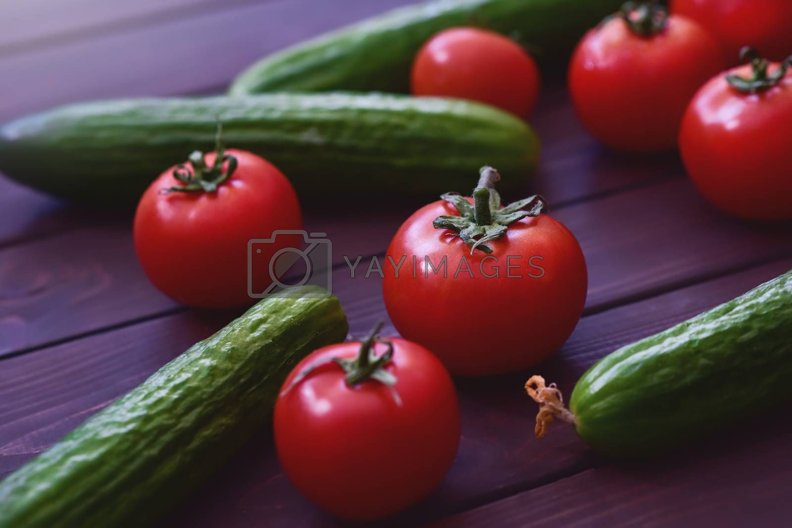 Fresh vegetables lie on a wooden table. Tomatoes and cucumbers by Nickstock