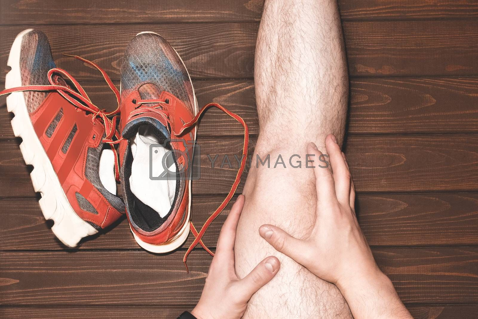 young sport man with strong athletic legs holding knee with his hands. in pain after suffering ligament injury during a running workout training on wooden background.