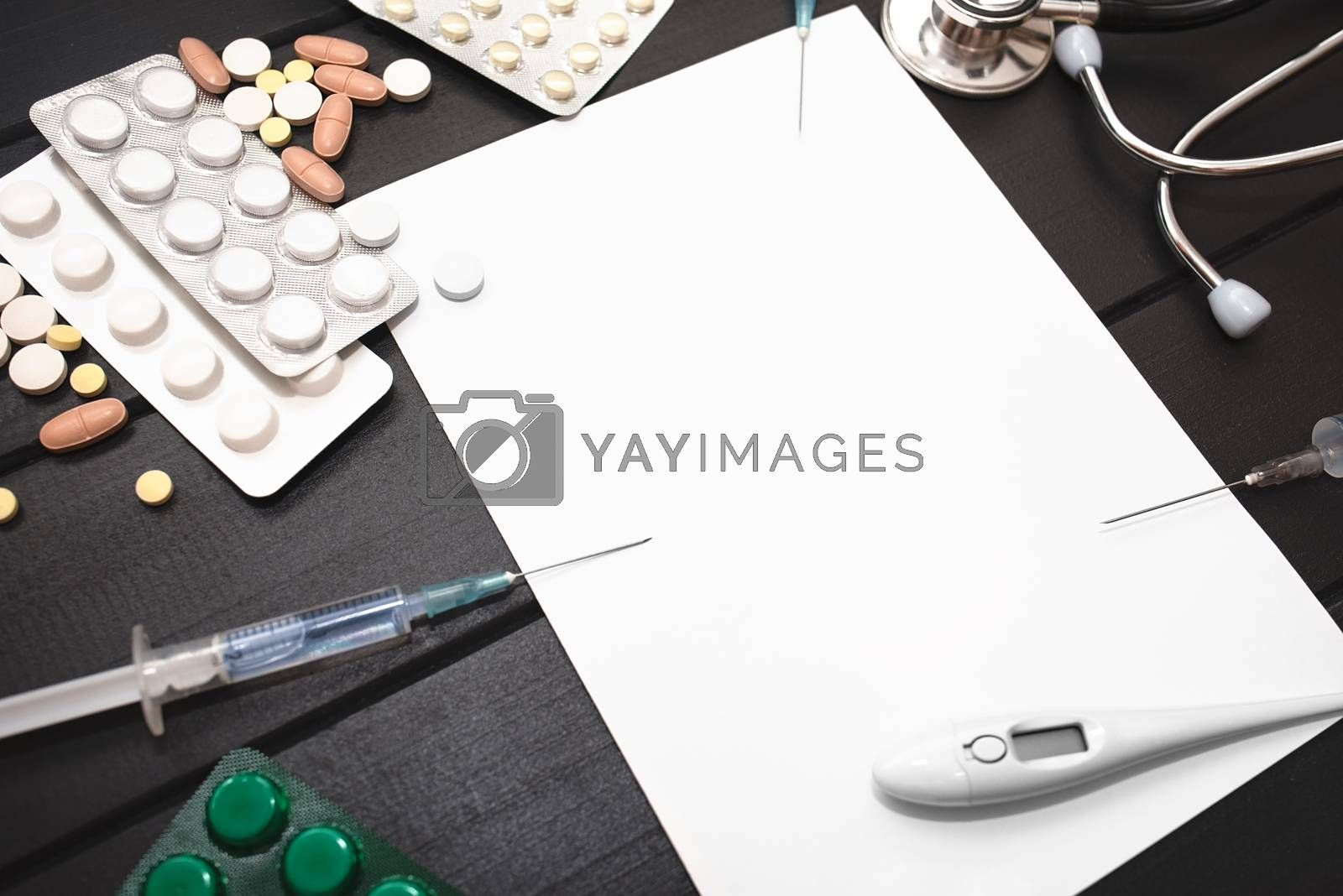 Medication prescription with pills and stethoscope lies on wooden table. Tablet or drug. Medicine and healthy concept. Copy space for text. Close-up. Indoors.