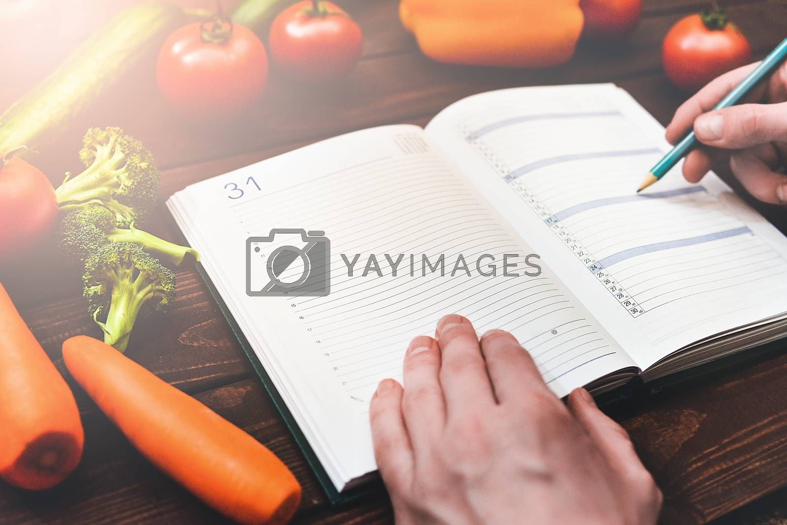 Dieting concept with a notepad and pen surrounded by lots of healthy fresh vegetables.