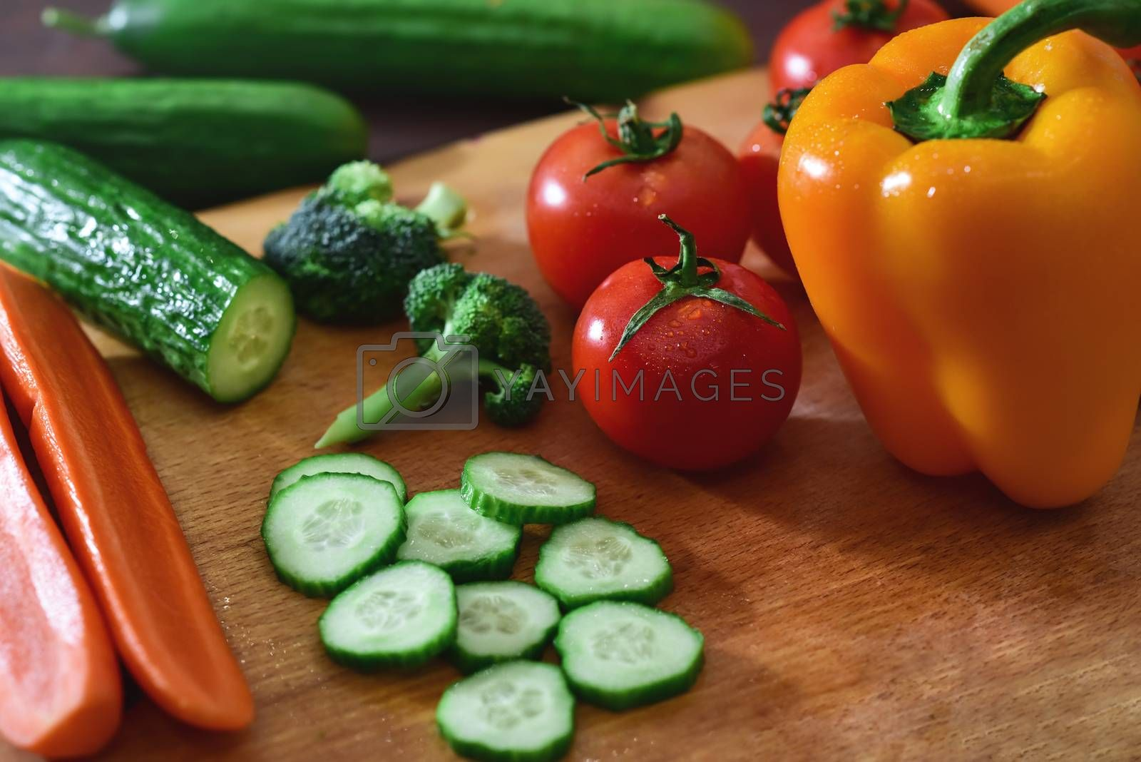 Nature Gifts. Benefits for the body. Fresh sliced vegetables lie on a wooden table. Tomatoes .cucumbers. broccoli. pepper. carrots.