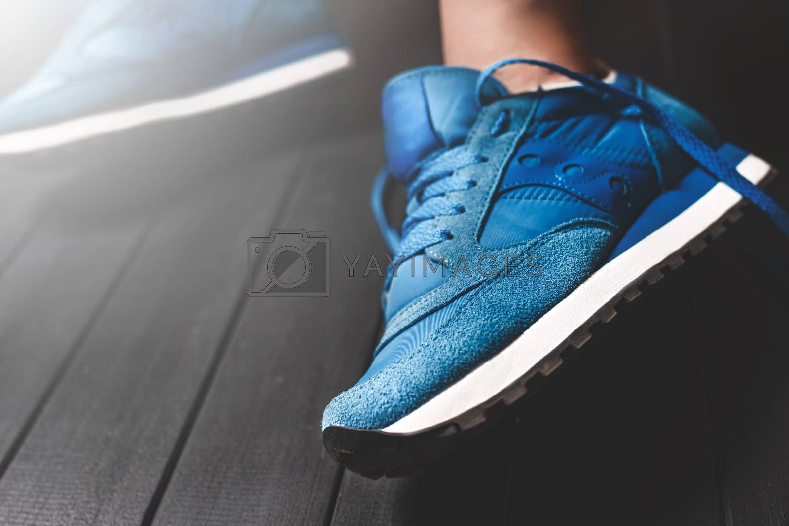 Close up women's legs on wooden background, blue Sneakers ,Women's shoes,spot focus.