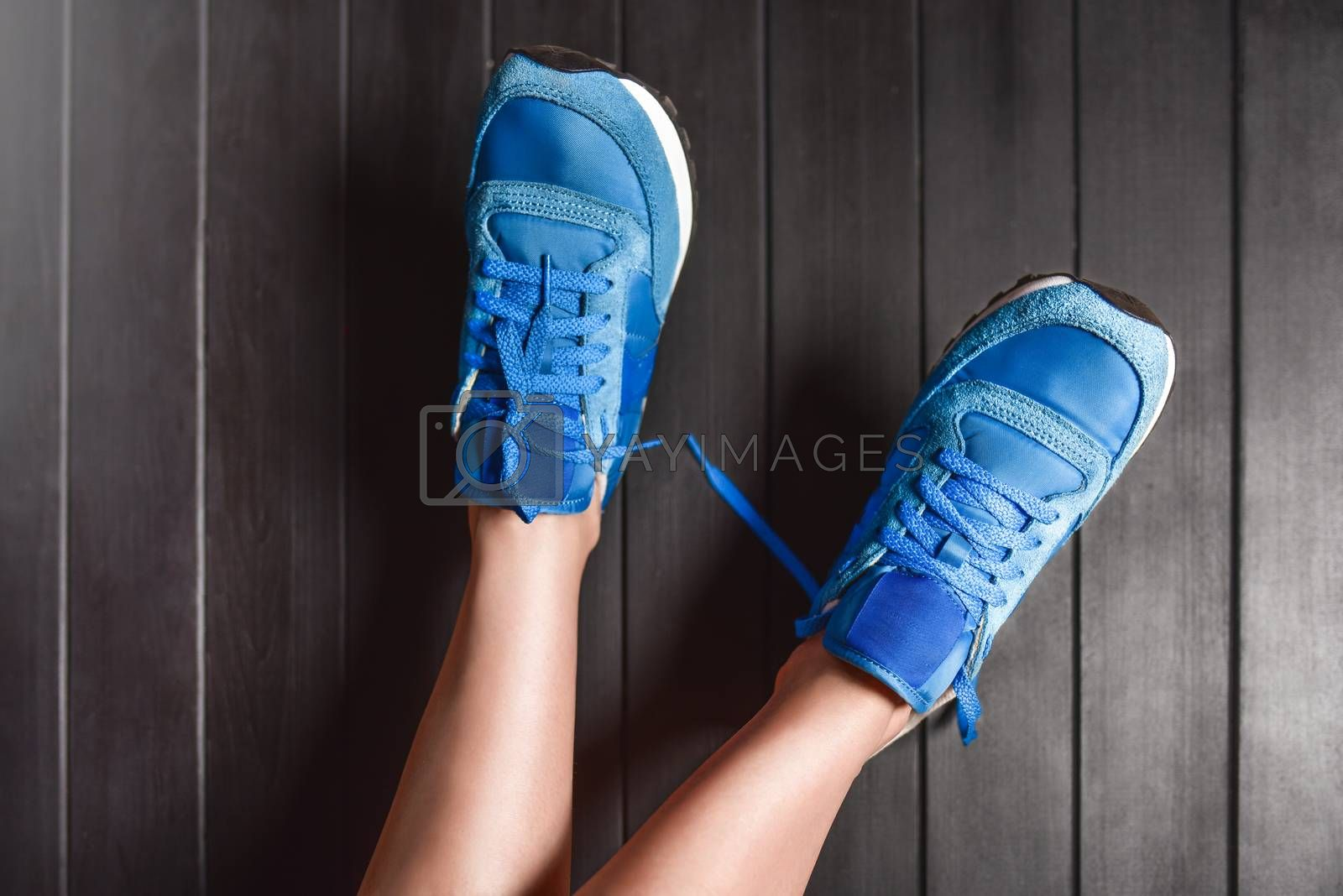 Close up fashion image of woman's feet, wearing sport sneakers on wooden background. lazy woman concept . rest concept
