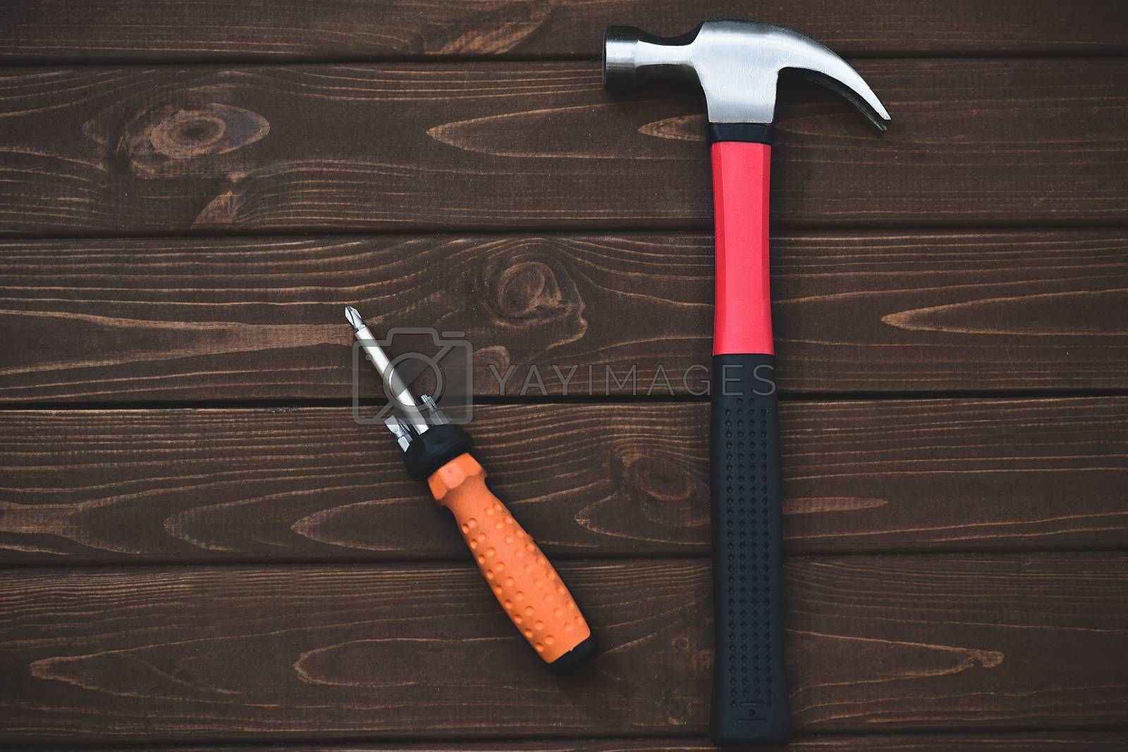 close-up tools as hammer and screwdriver on a wooden background. work concept. free copyspace by Nickstock