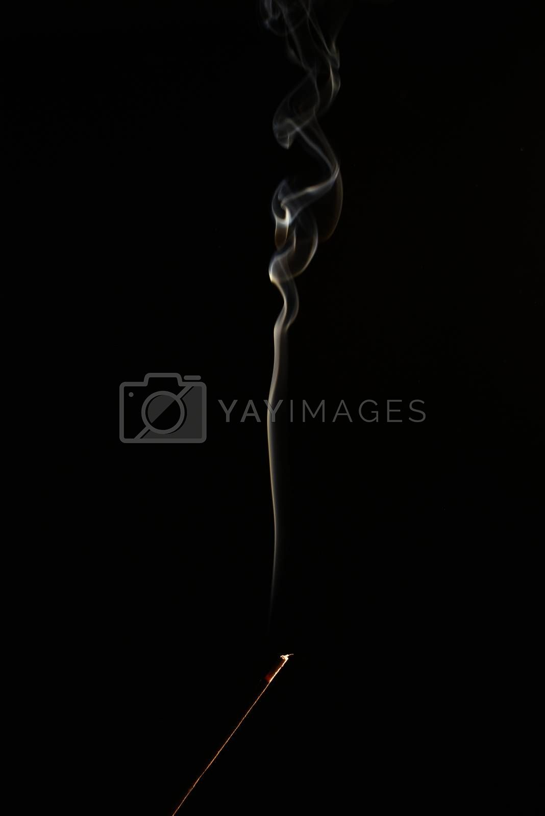 smoldering aromatic stick in the dark,a lot of smoke by Nickstock