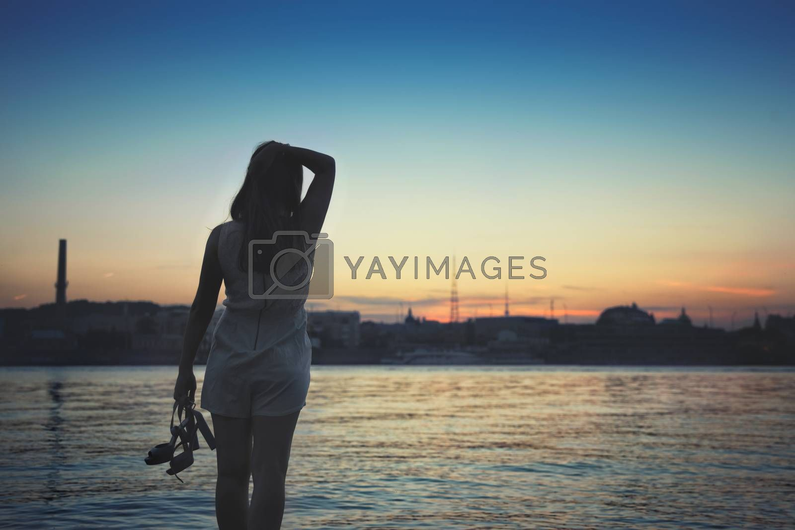 girl standing on the beach, watching the sunset