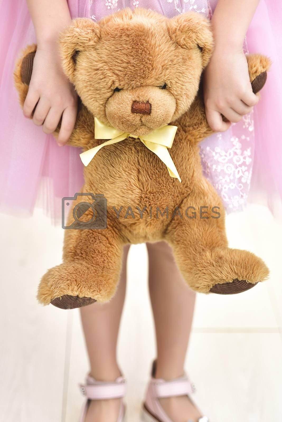 Child in wedding dress with bear. Close up White background