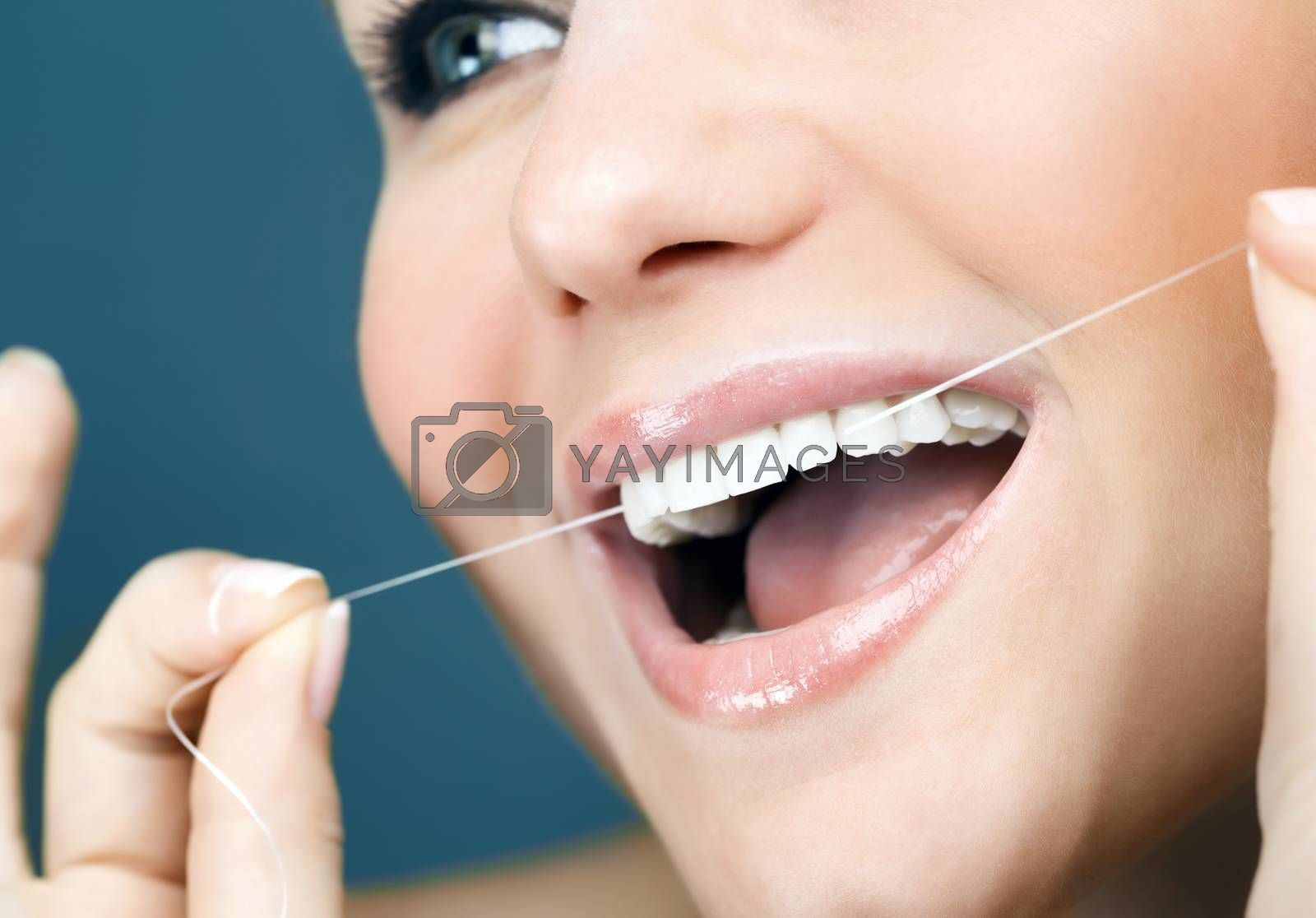 Closeup photo of a nice female with perfect white teeth using dental floss, oral care, healthy lifestyle, hygiene concept