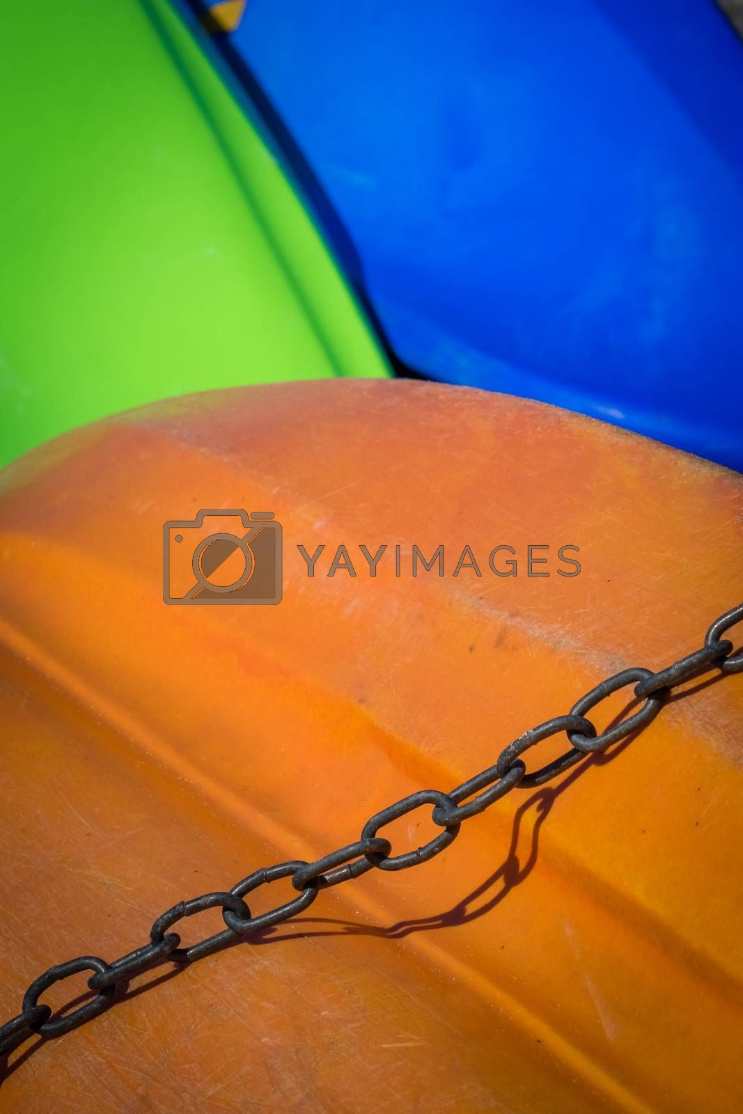 Chain with a colorful background of boats on a shore