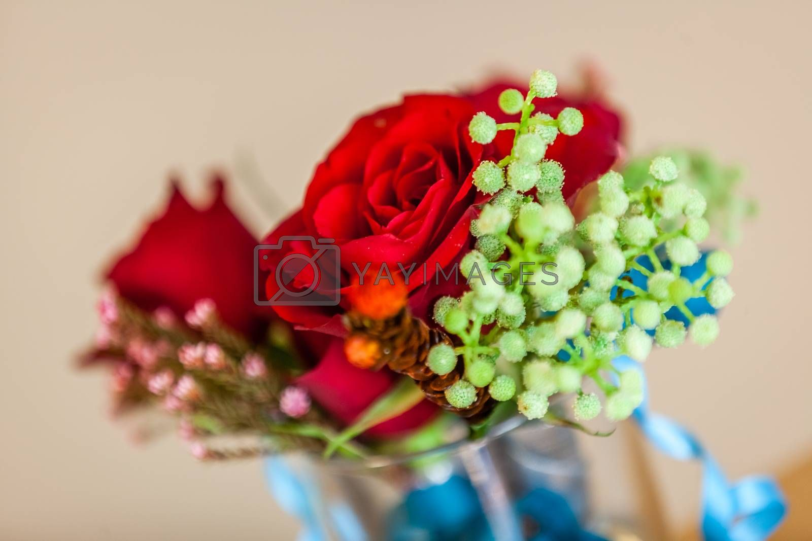 Red roses wedding bouquet in glass holder on table