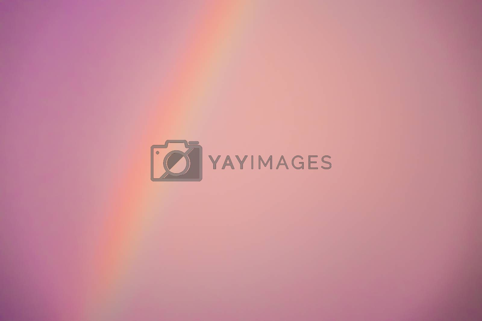Blurred abstract pinkish background of a rainbow and the sky