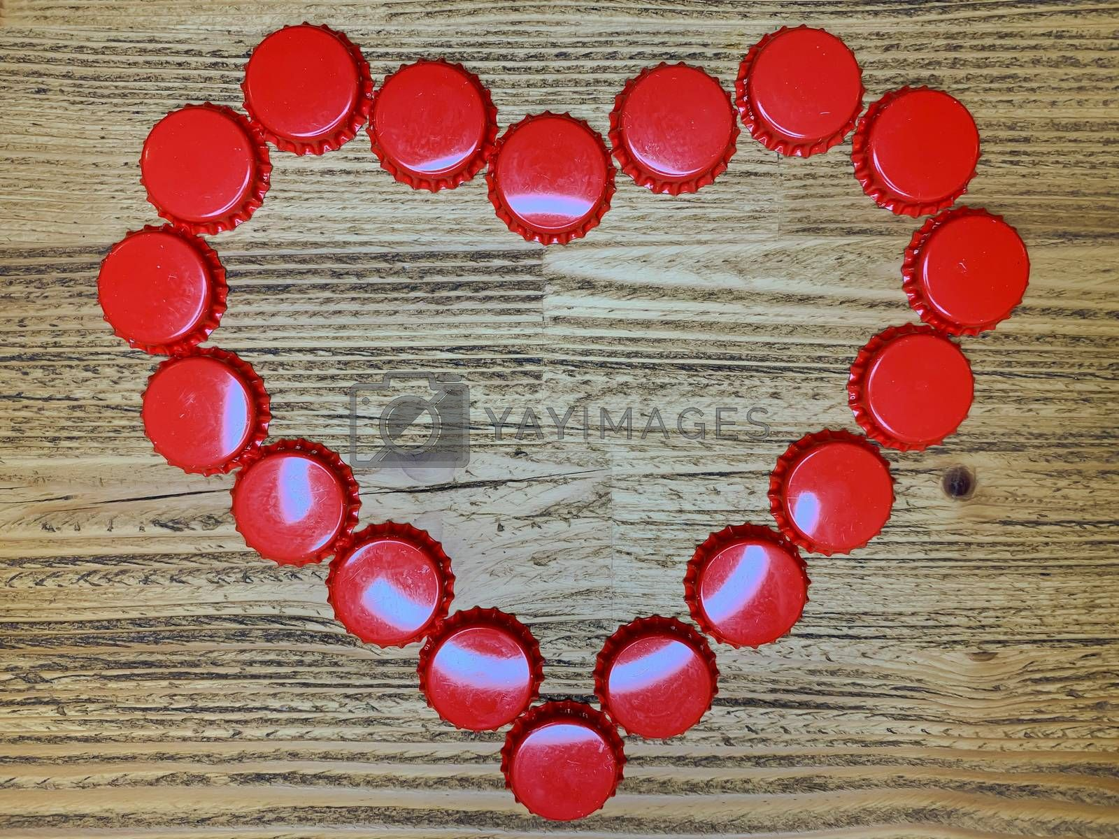 Red love heart made from beer bottle tops lids on a rustic wooden table. Beer drinkers Valentine's day concept, top view horizontal stock image.