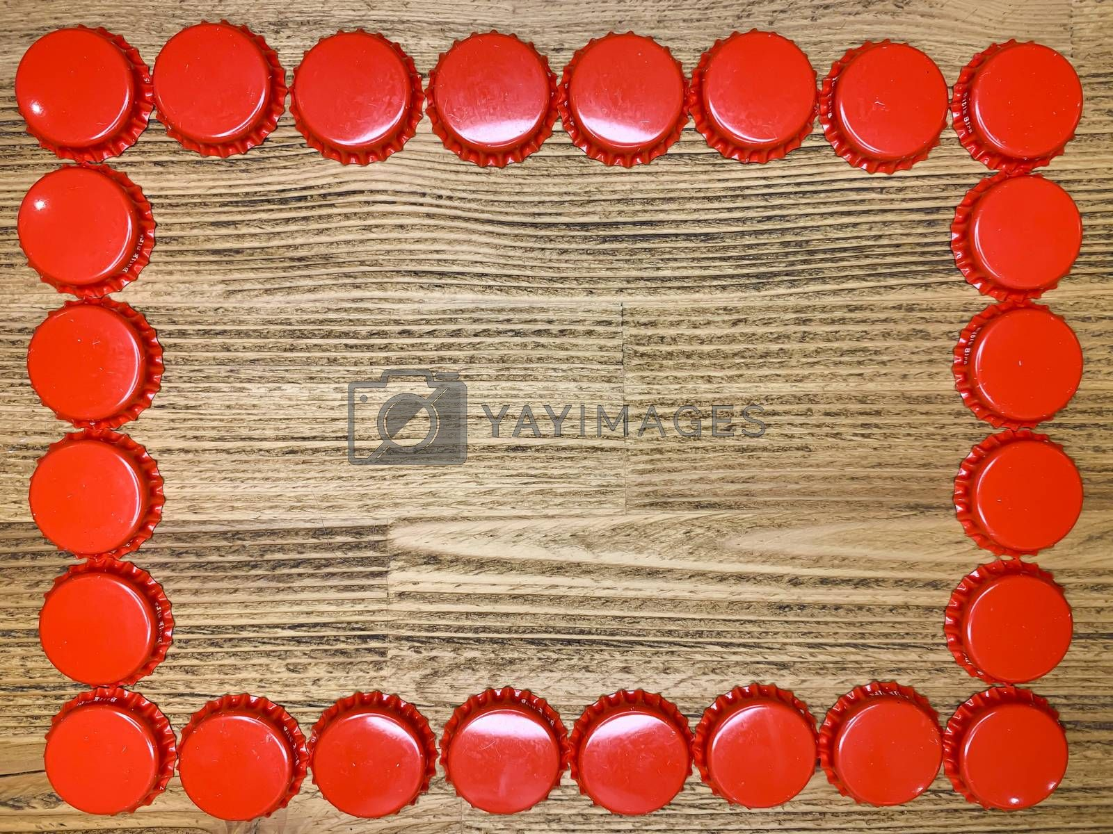 A frame made from red beer bottle tops lids on a rustic wooden table. Beer drinkers postcard concept, top view horizontal stock image with empty space for text