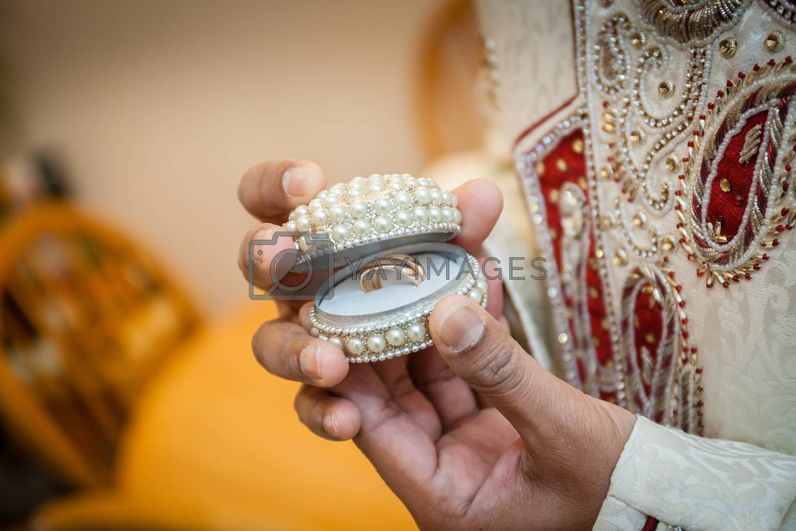 Indian groom showing open box containing wedding rings