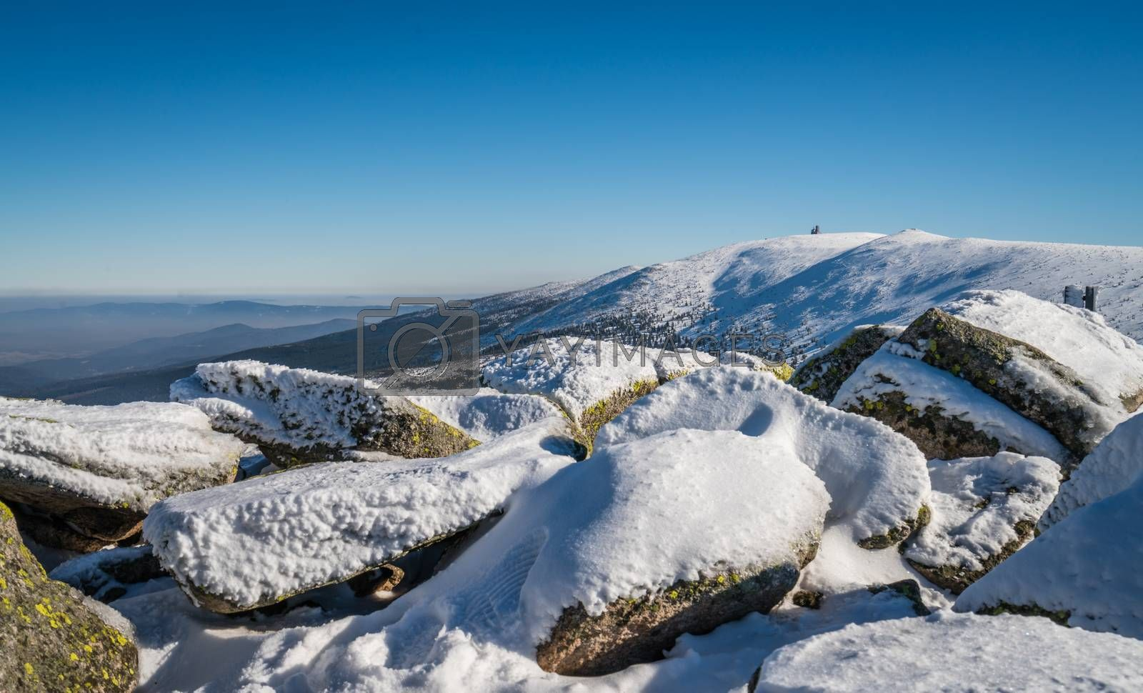Large rocks in the foreground of a winter landscape of a Karkonosze mountains as seen from the Szrenica mountain, Poland