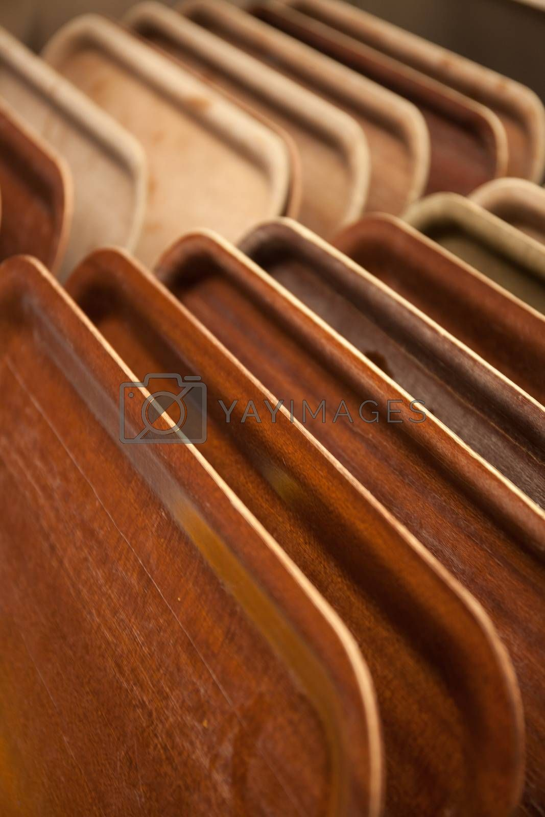 Row of wooden trays used for carrying plates with food in a canteen