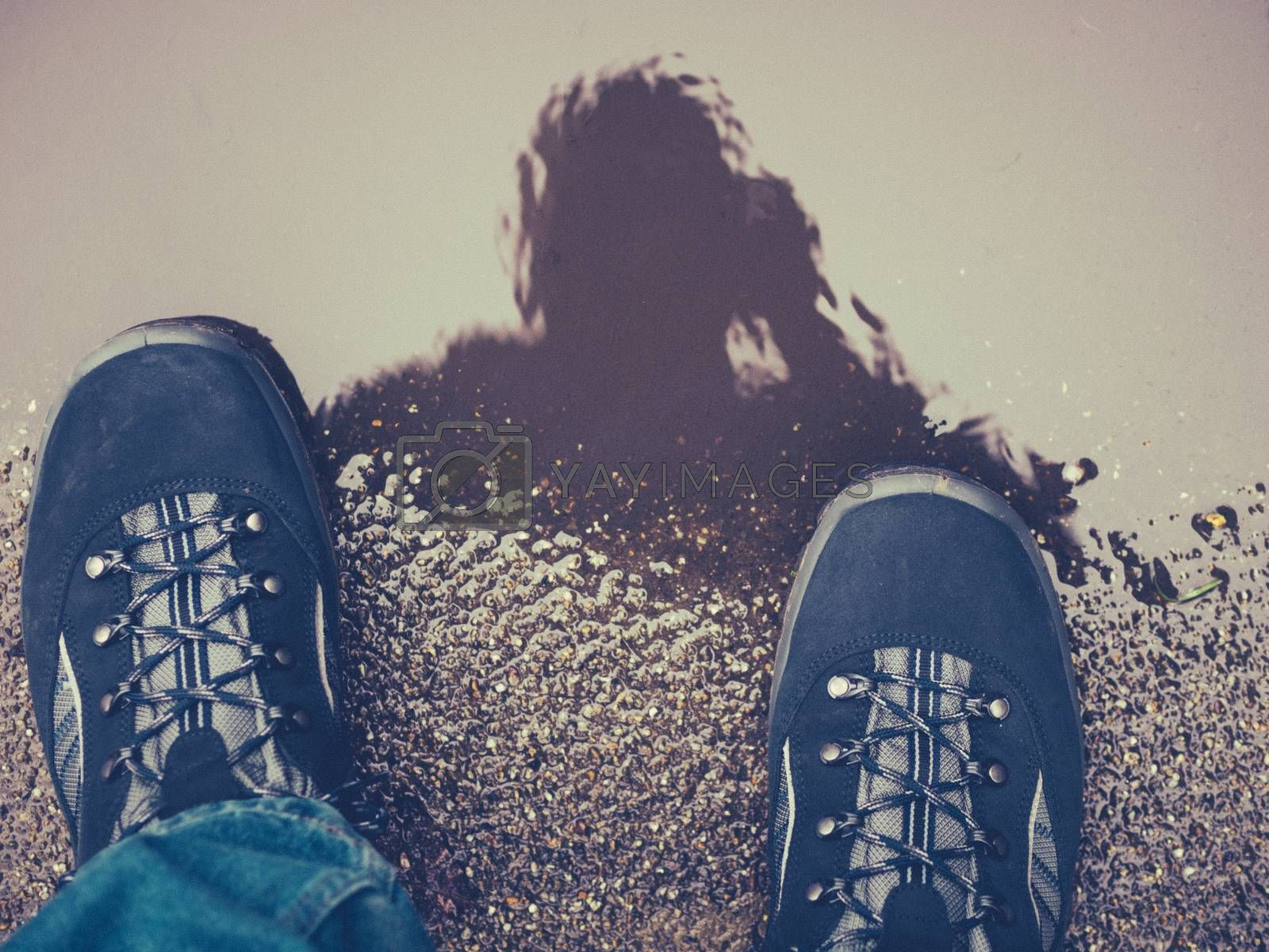 Close up of mans feet in shoes standing on a street and taking picture of a puddle