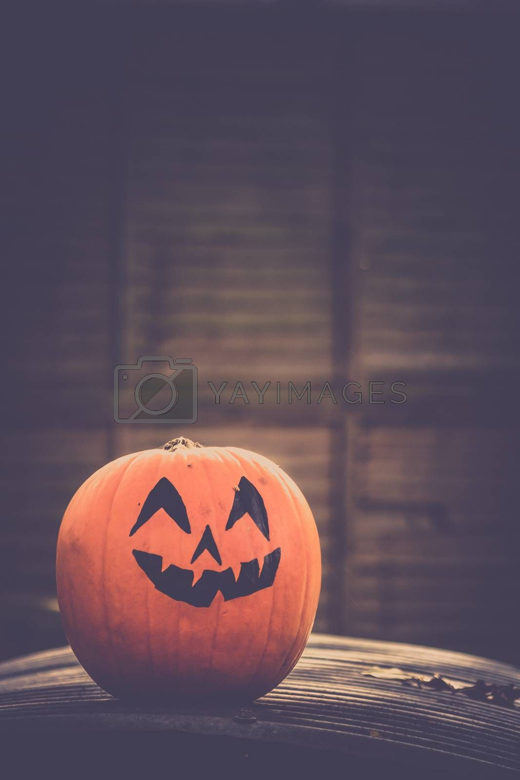 Large pumpkin with a scary face drawing on it
