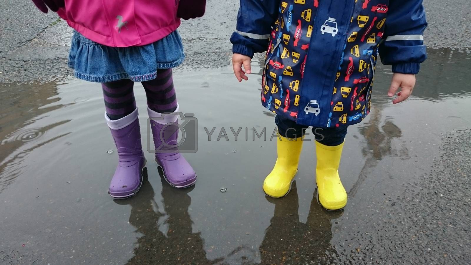 Boy and girl standing in the puddle on the street after the rain