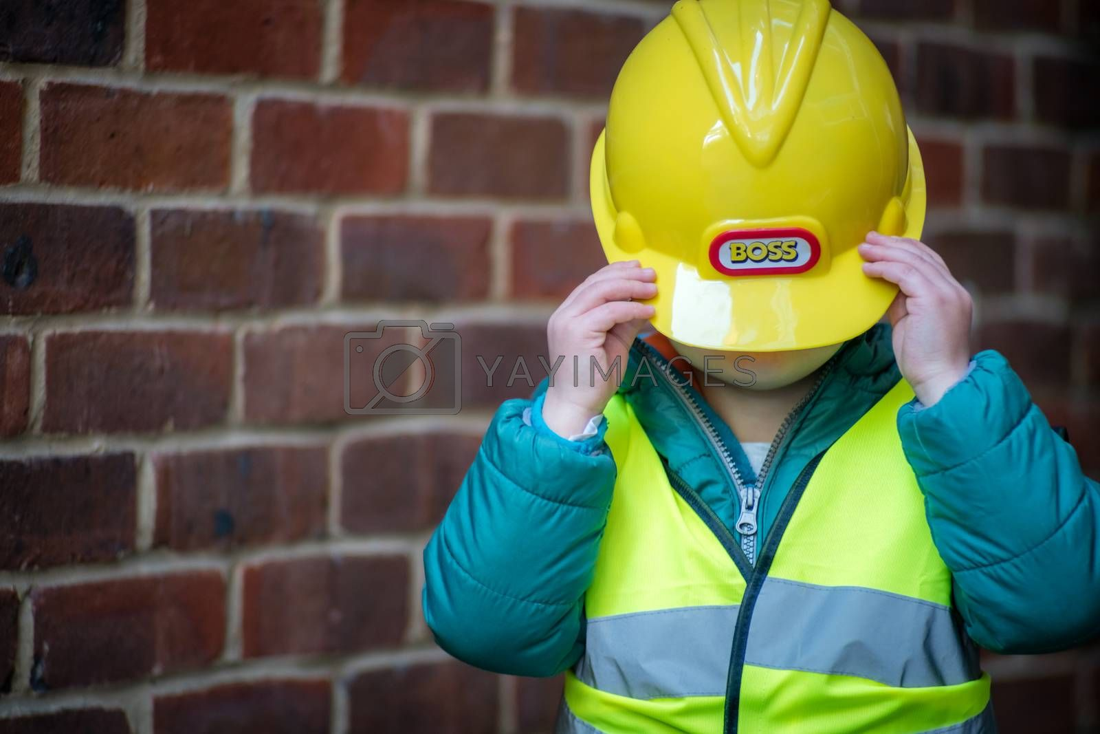 Little cute boy pretending to be a builder foreman outside his home