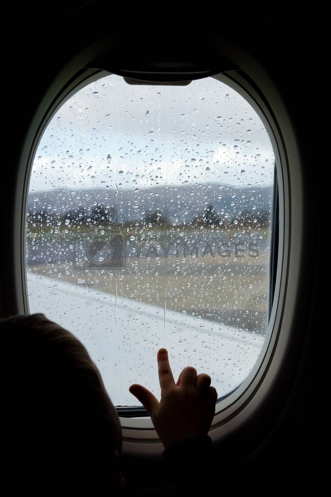 Little boy looking through the plane window before take off in the rain