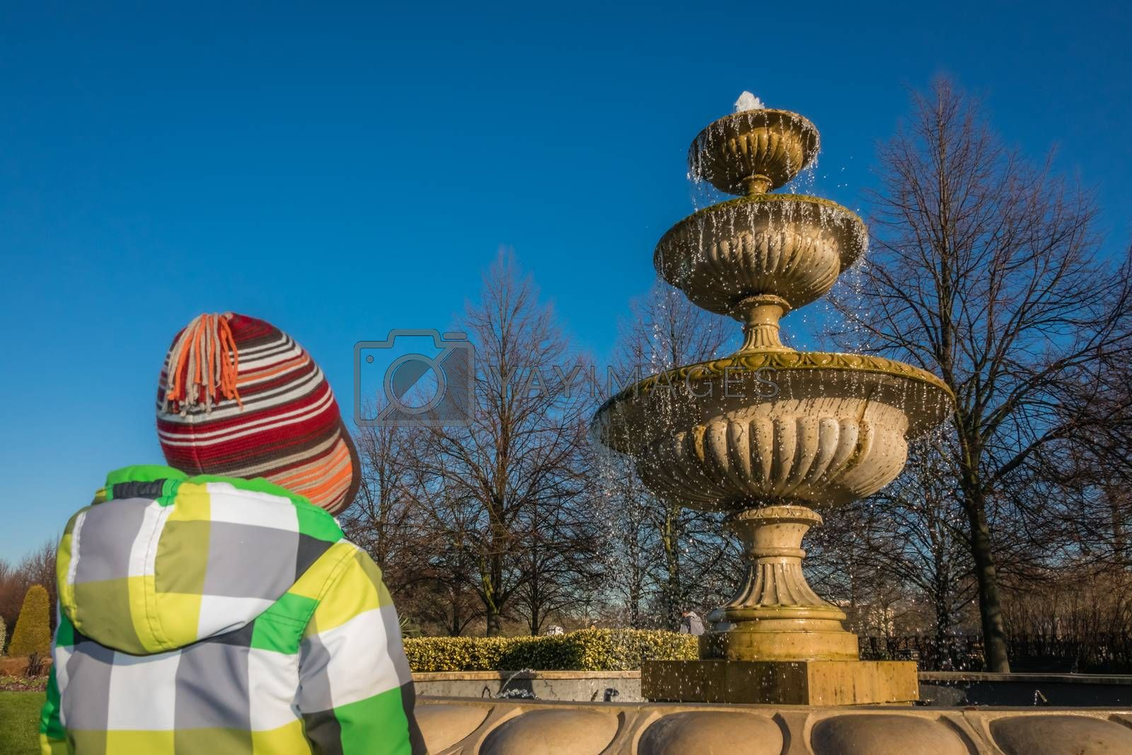 Little boy looking at the Fountain in Regents Park , London, UK