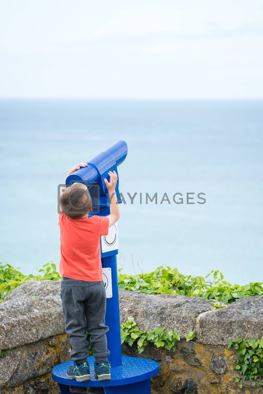 Little boy stretching to to be able to look through the telescope on the viewing platform in Cornwall, UK