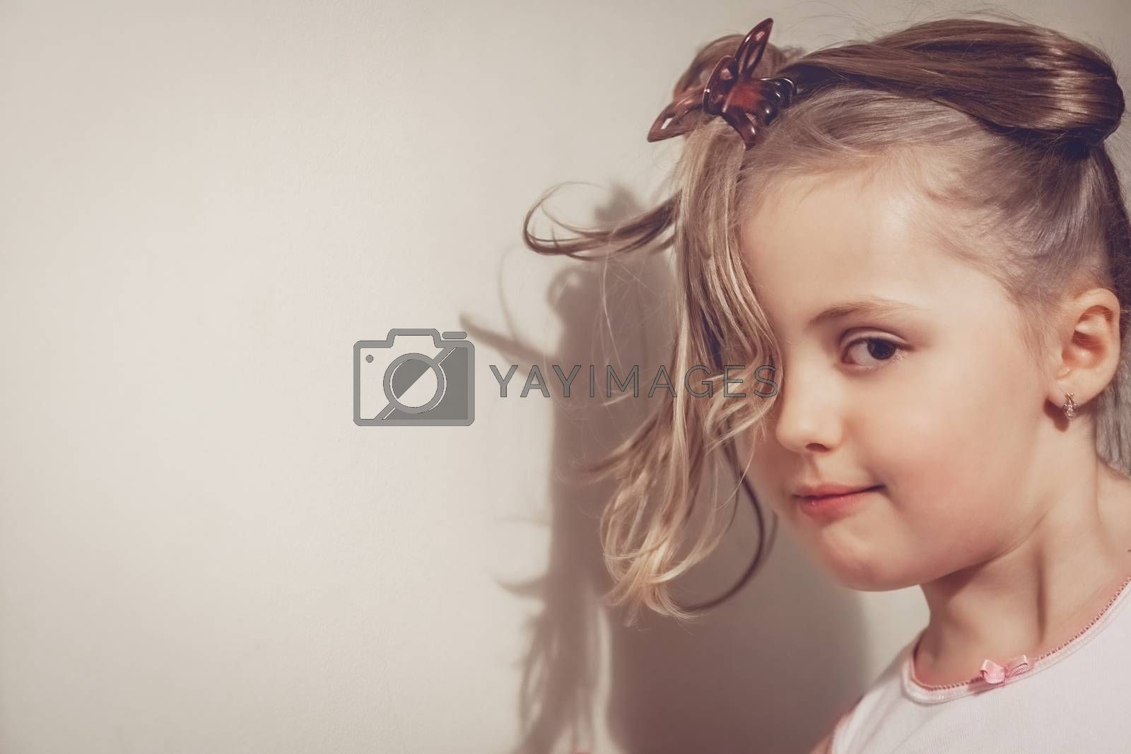 Portrait of a cute young Caucasian little girl with tied hair