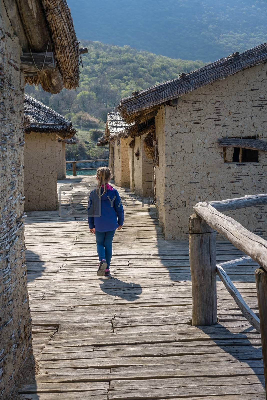 Little Caucasian girl walking among mud and straw houses in the Bay of the bones museum on water, authentic reconstruction of the pile dwelling settlement, Ohrid, Republic of Macedonia