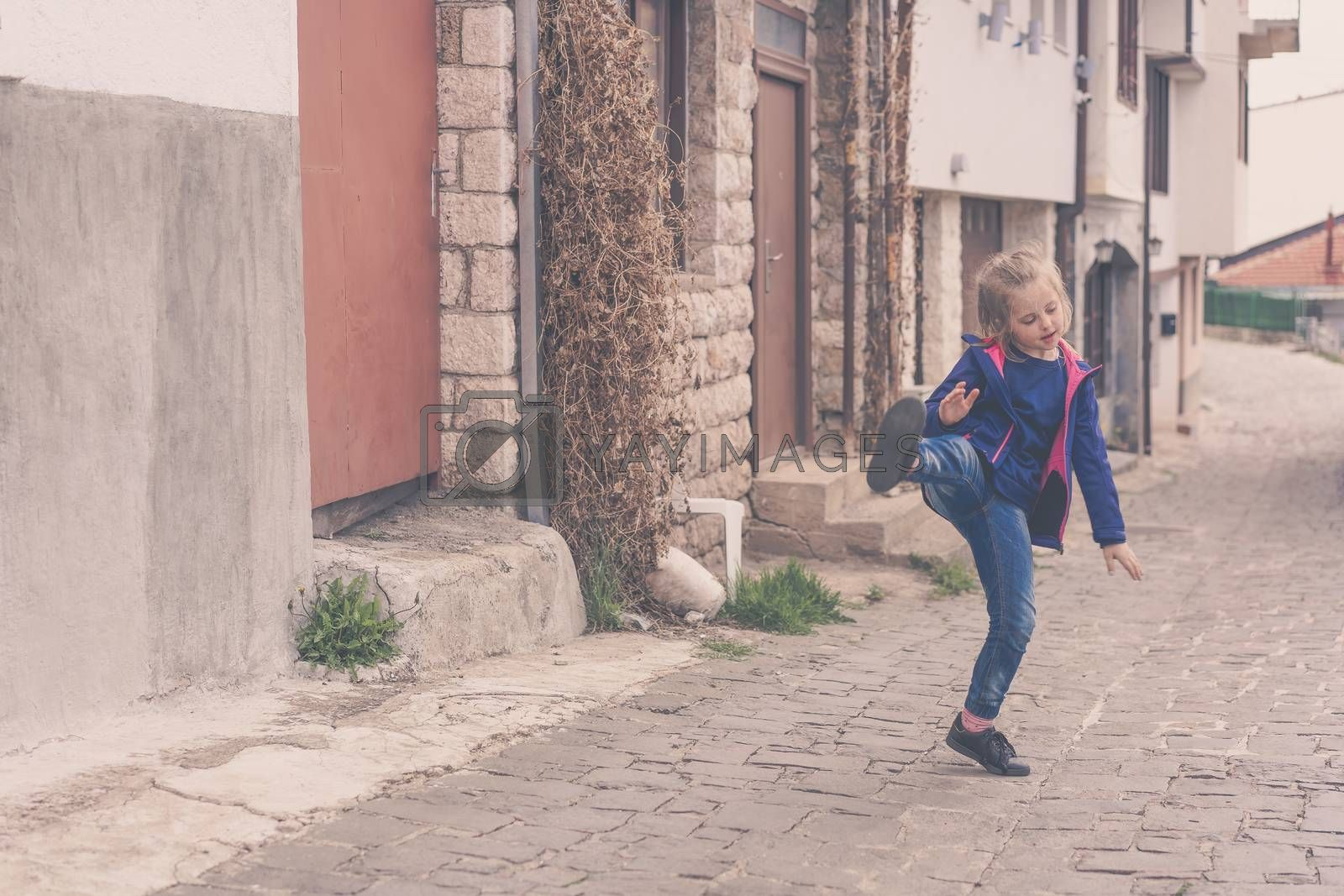 Little girl having fun practising kicks on a street in Ohrid, Northern Macedonia