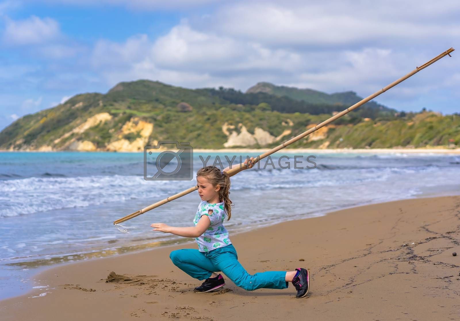 The girl training martial arts with the long wooden stick on the beach in summer