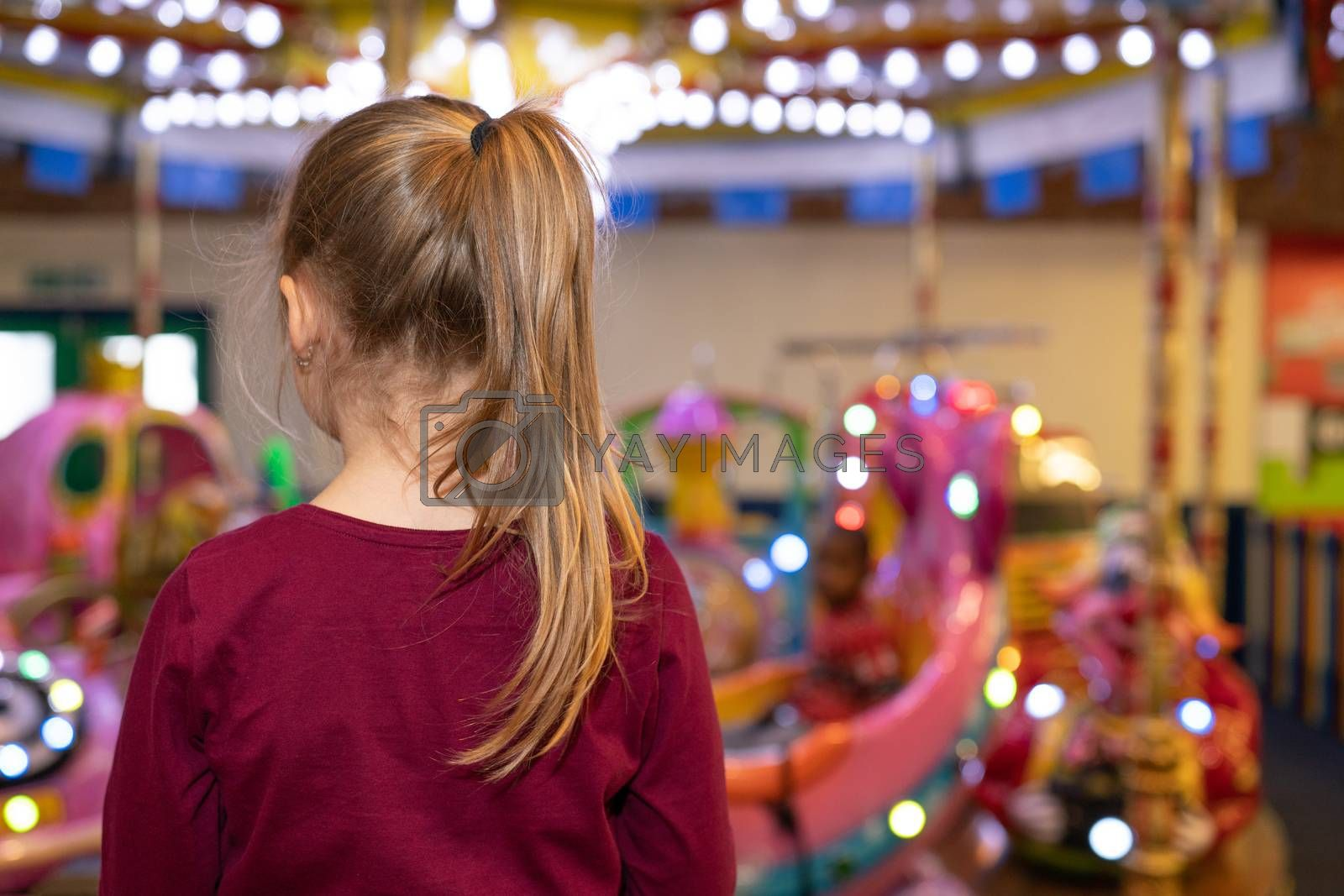 Cute young girl with a ponytail looking at a carousel in an indoor funfair amusement playground