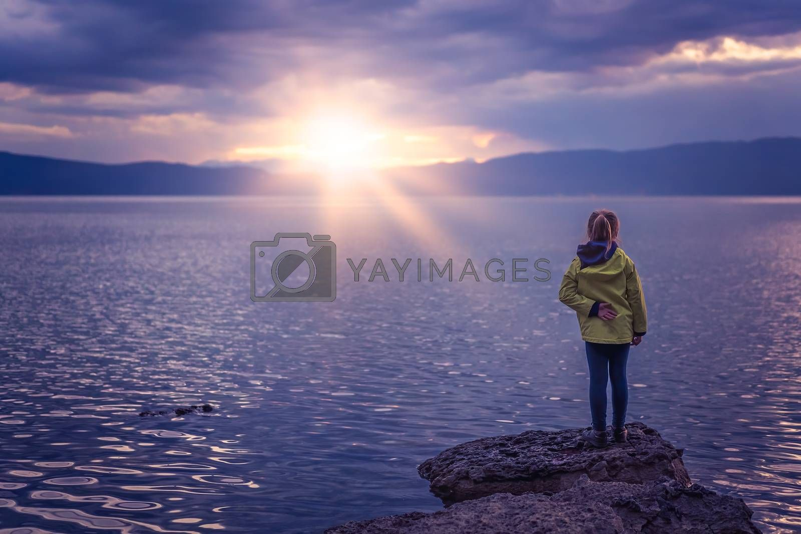 Little girl standing on the large boulders on the shore of Lake Ohrid, Republic of Macedonia