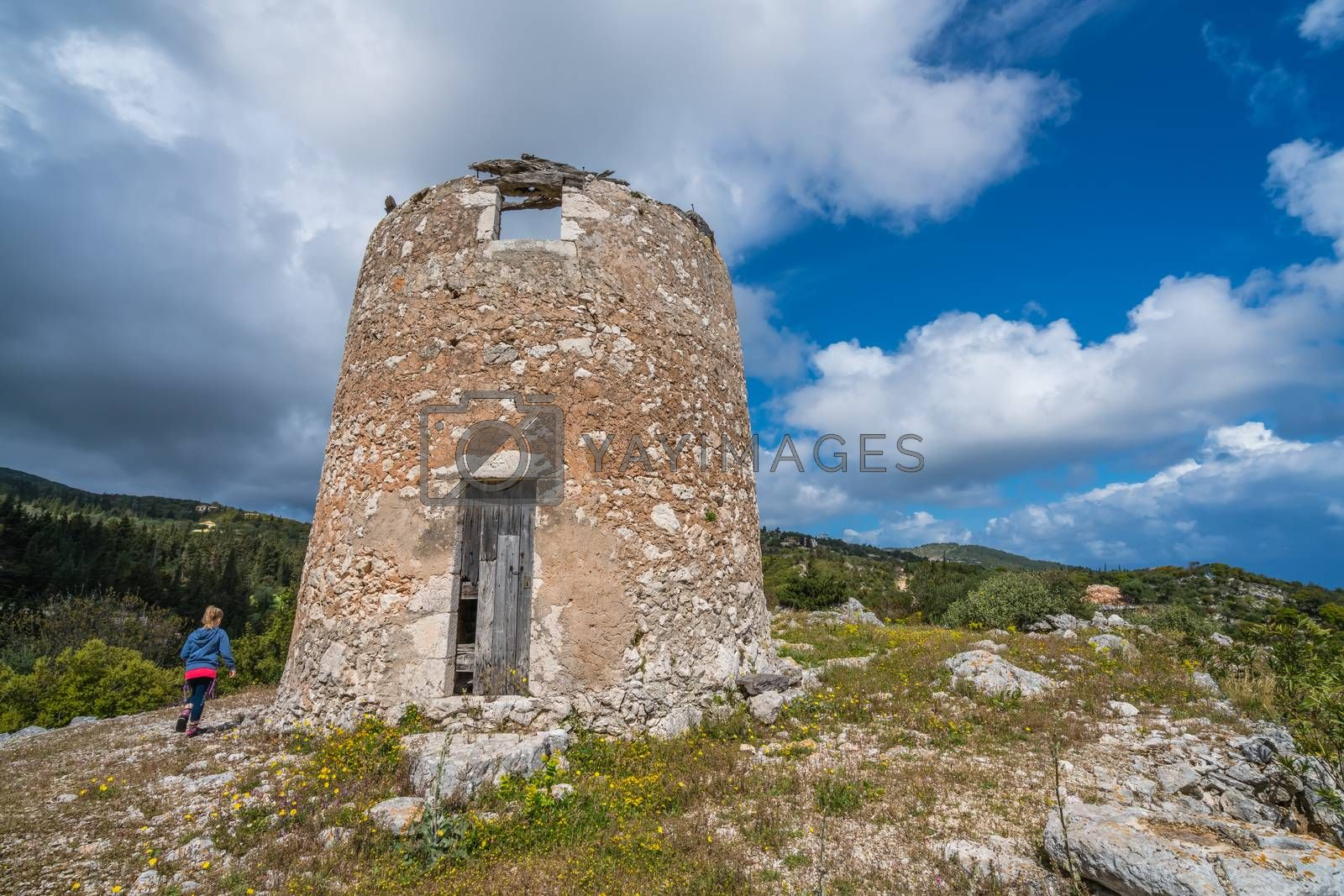 Young girl running towards the remnants of an old windmill in Askos, Zakynthos island, Greece