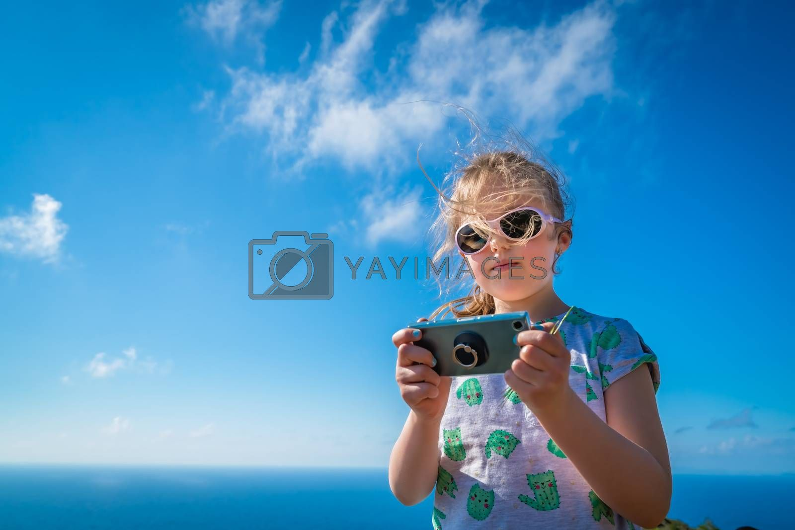 Cute little blond Caucasian girl playing with mobile phone on the beach in summer