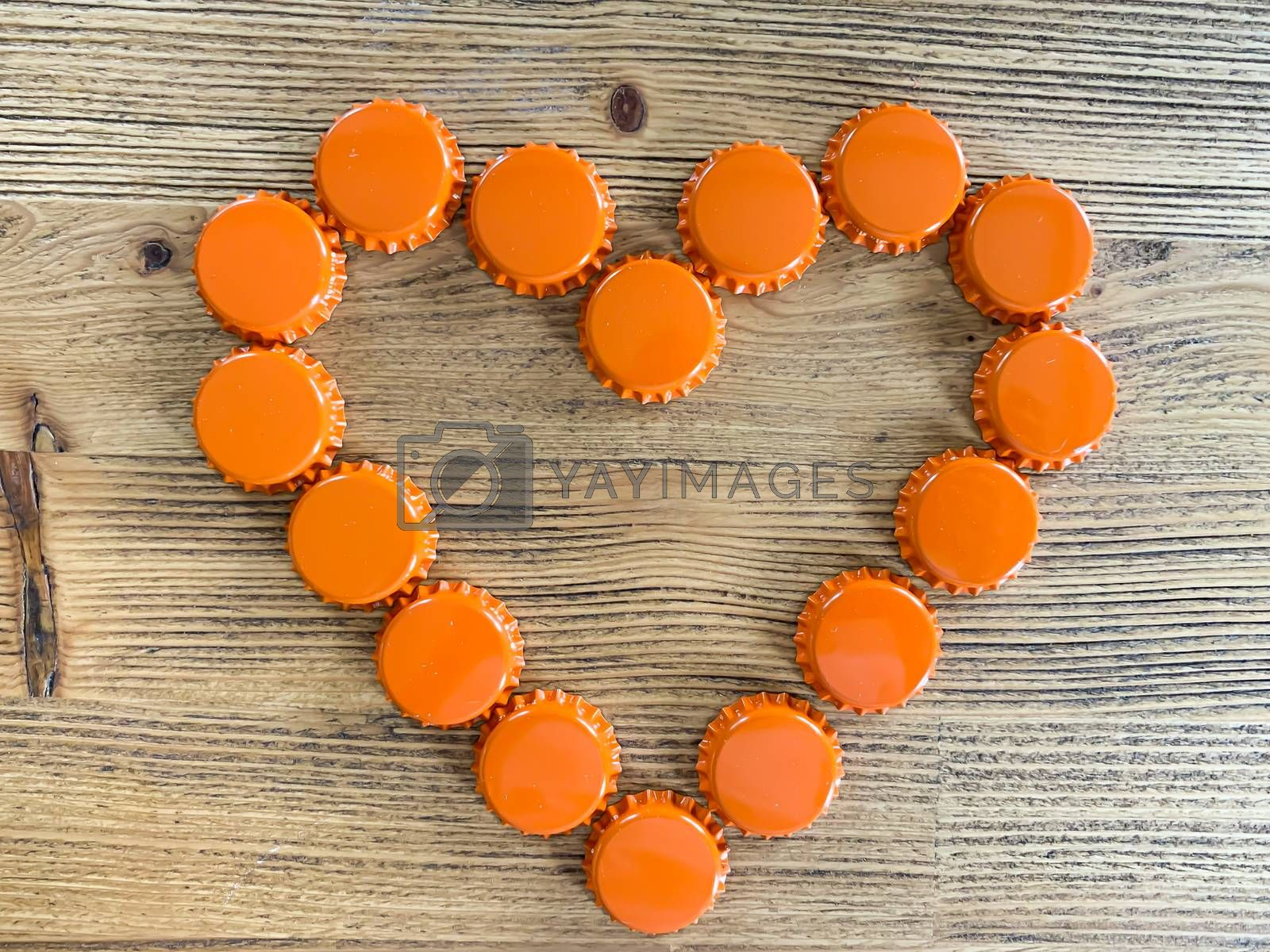 An orange love heart made from beer bottle tops lids on a rustic wooden table. Beer drinkers Valentine's day concept top view with empty space for text horizontal image