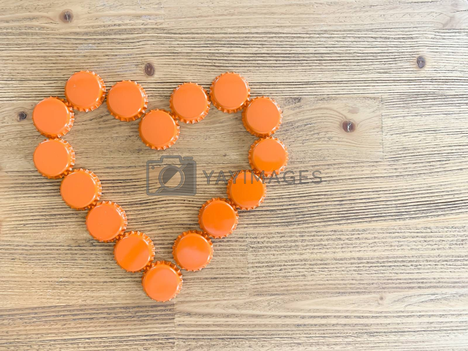 An orange love heart made from beer bottle tops lids on a rustic wooden table. Beer drinkers Valentine's day concept top view horizontal image with empty space for text