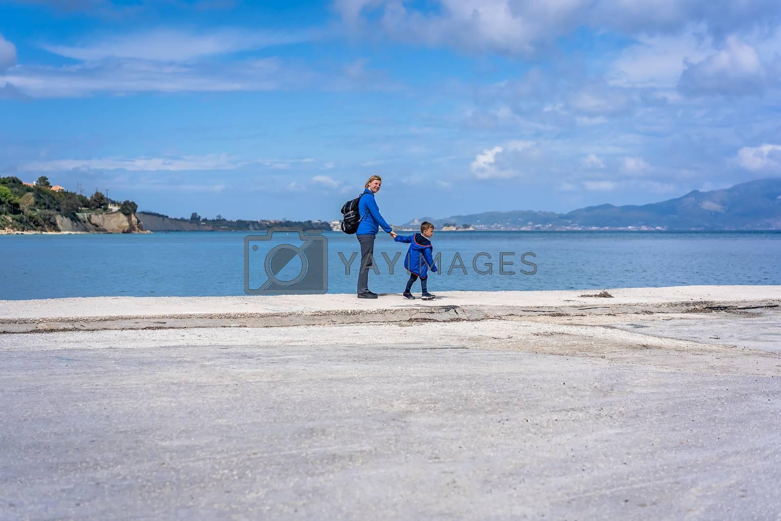 Mother and son walking on the concrete shore in Port Sostis, Zante Zakynthos Island, Greece